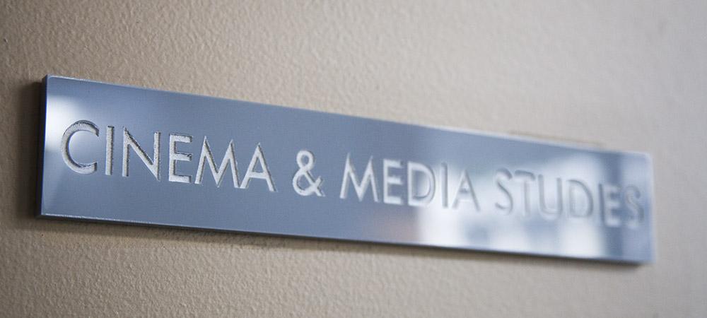 rectangular gray plaque with white text reading CINEMA & MEDIA STUDIES
