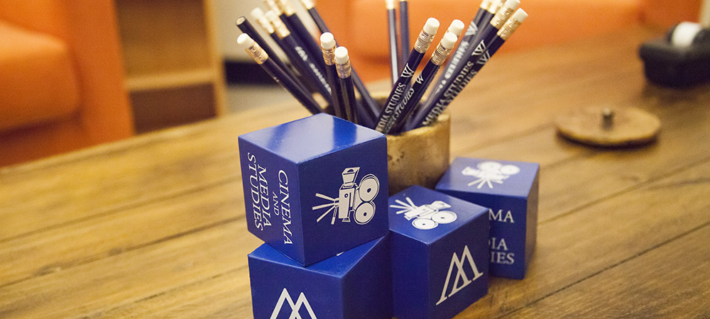 photo of cup with dark blue CAMS pencils and stacked blue blocks with the Wellesley W and CINEMA & MEDIA STUDIES in white