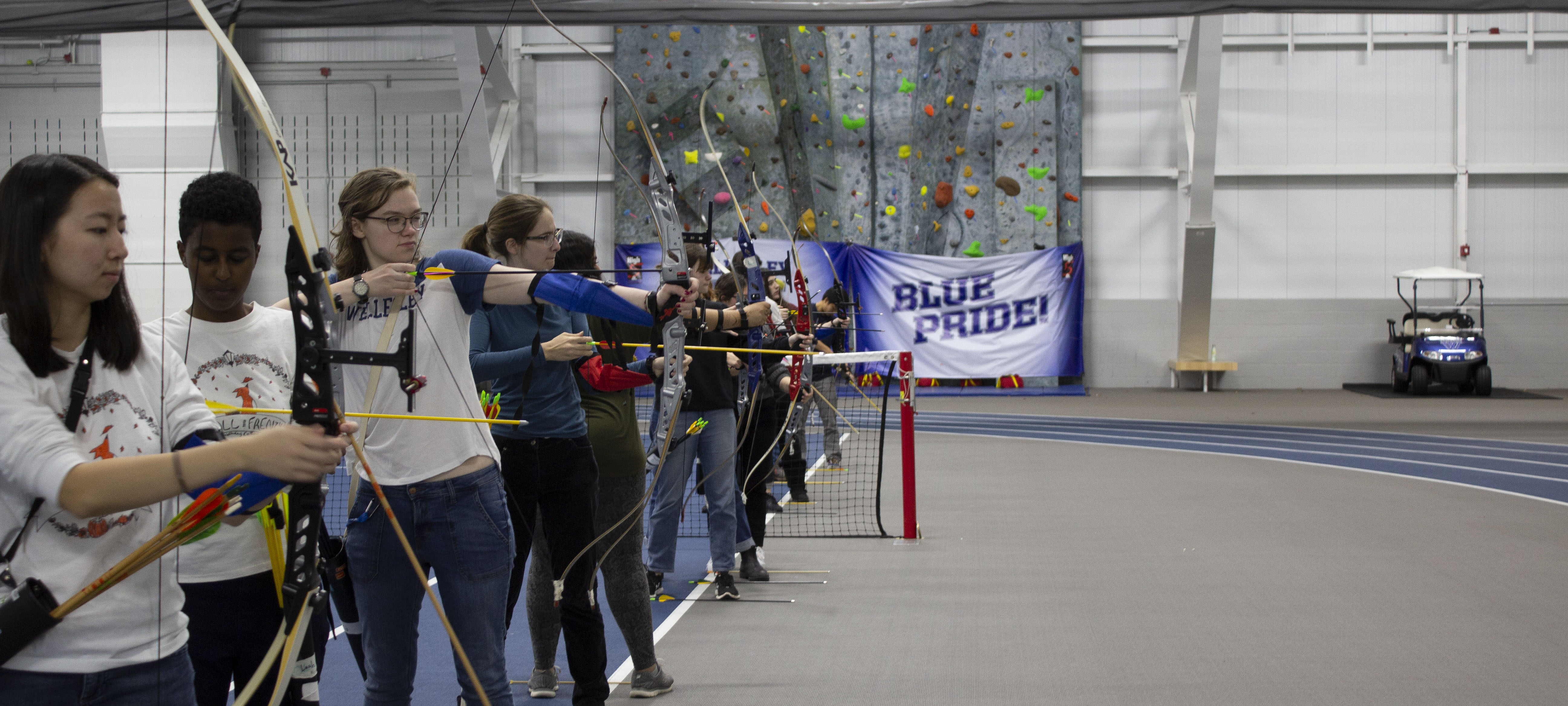 Students are lined up with bow and arrows inside the KSC. Some have their bows drawn.