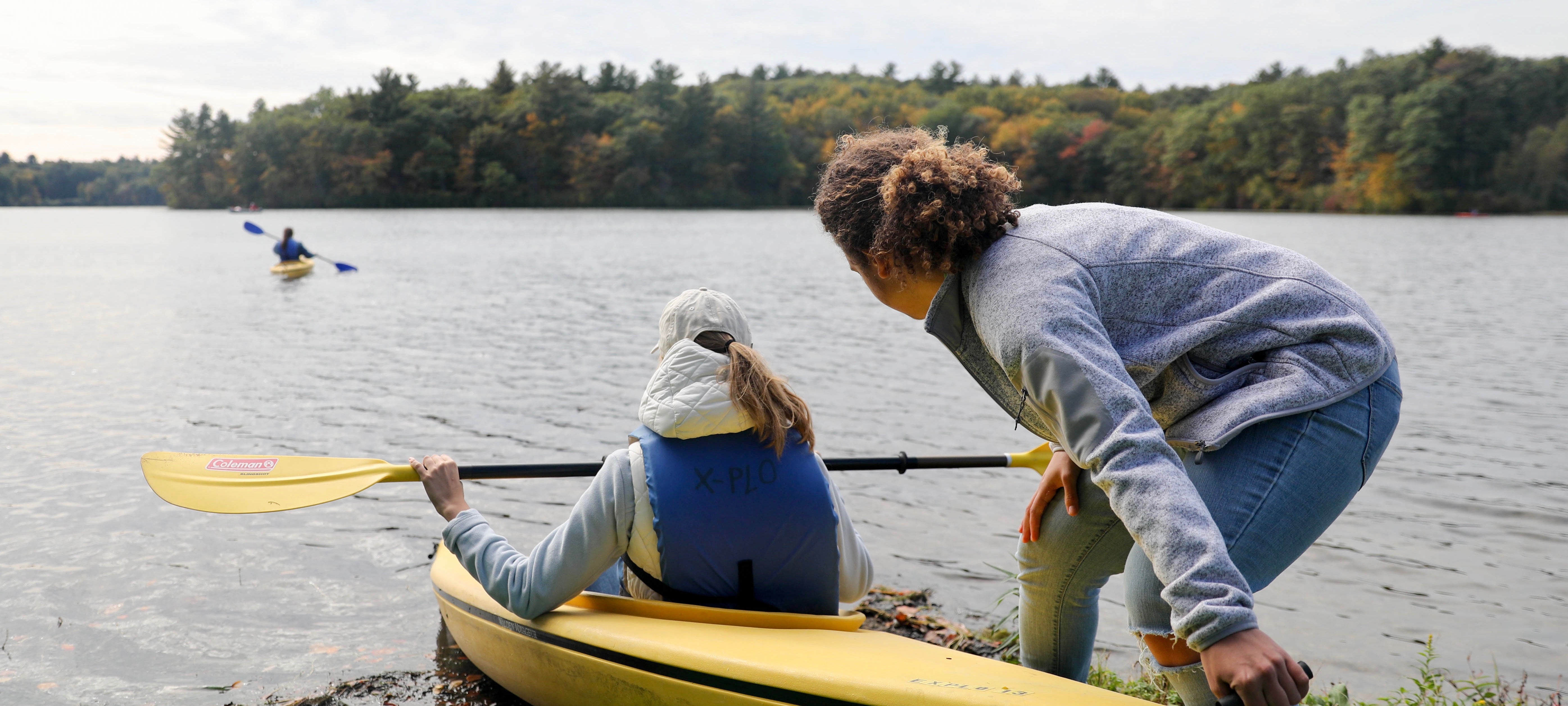 A student sits in a yellow kayak, wearing a blue life jacket. Another student is pushing them off from the shallow water.