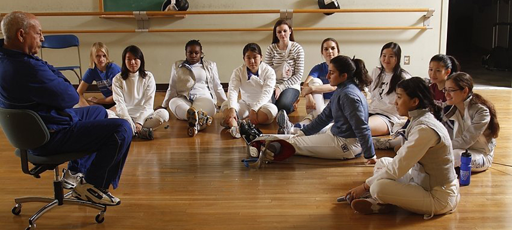 A group of student fencers gather around their coach