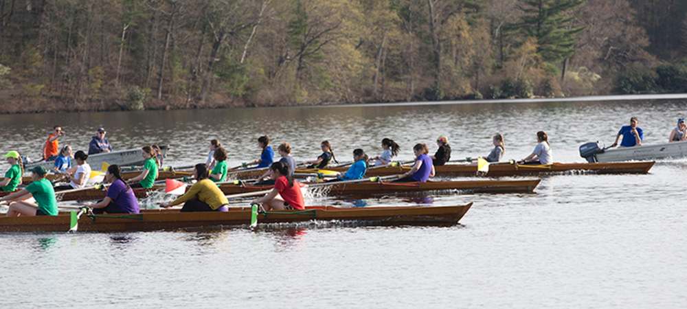 Dorms race past each other in a crew regatta on Lake Waban