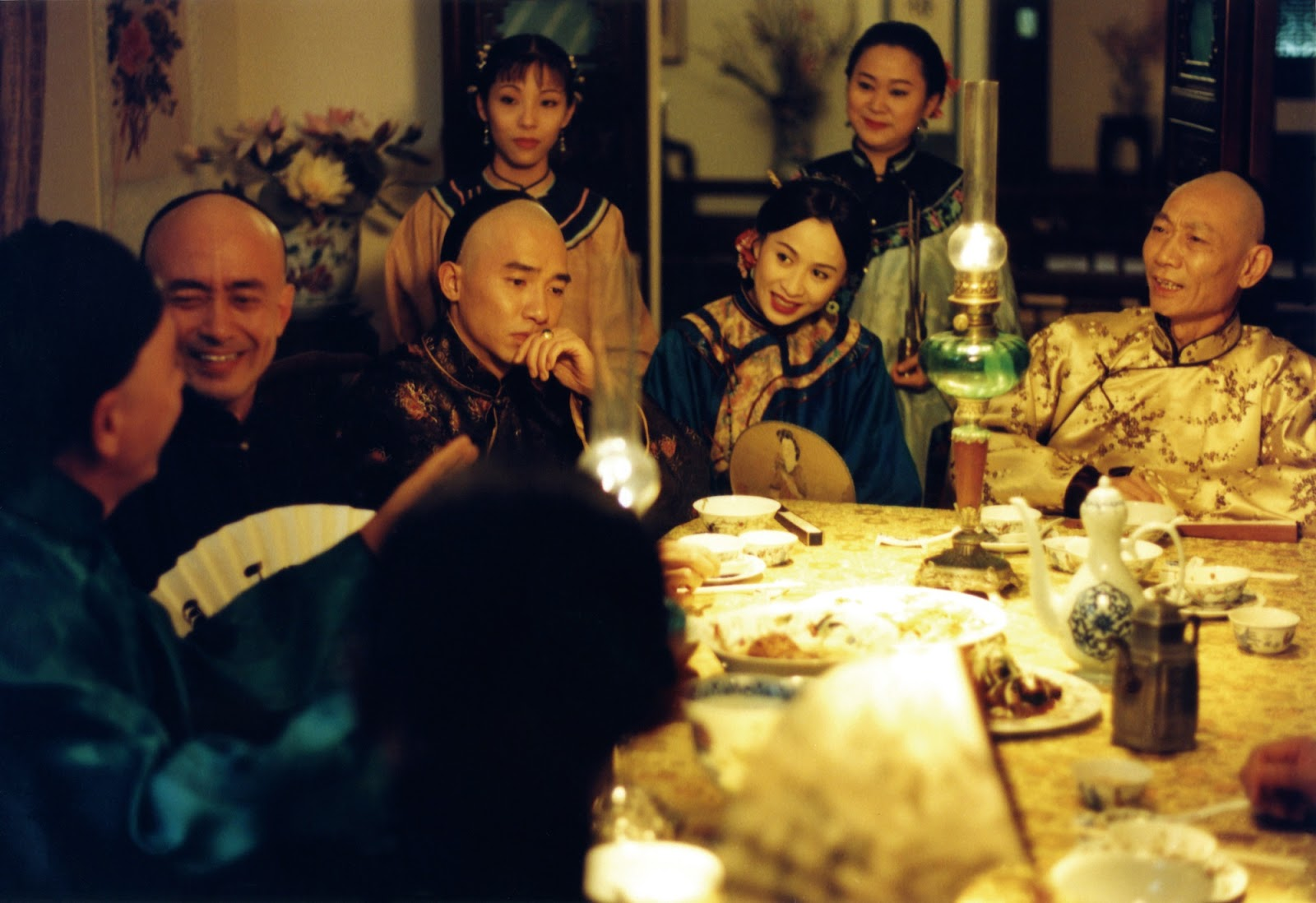 A still from the film Flowers of Shanghai, Around a table at a party, all guests appear to be smiling except one man
