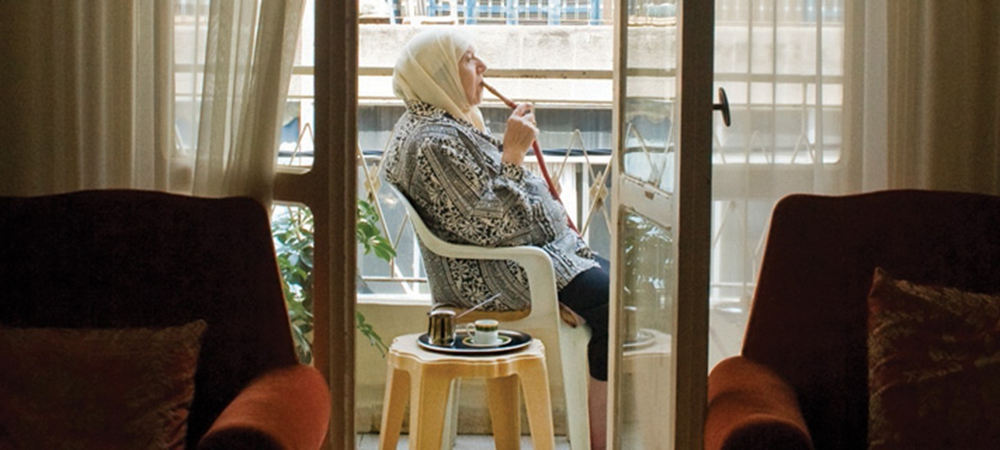 A still from the film Teta, Alf Marra. An old woman wearing a headscarf sits on an apartment balcony smoking from a hookah pipe.