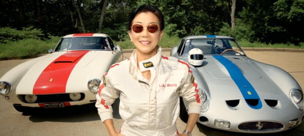 Lulu in front of race cars