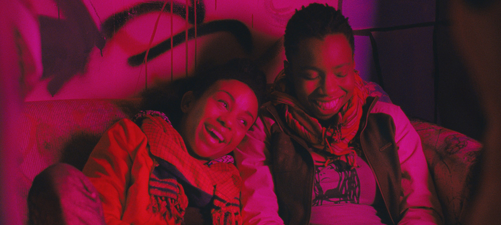 a still from the film Pariah, two women are sitting next to each other on a couch, laughing