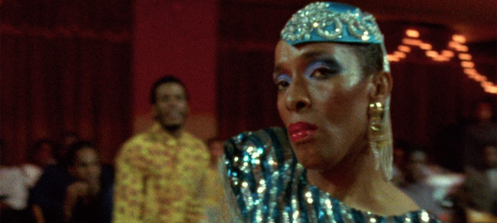 A still from the film Paris is Burning, a performer in drag gives the camera a look while competing in a ball