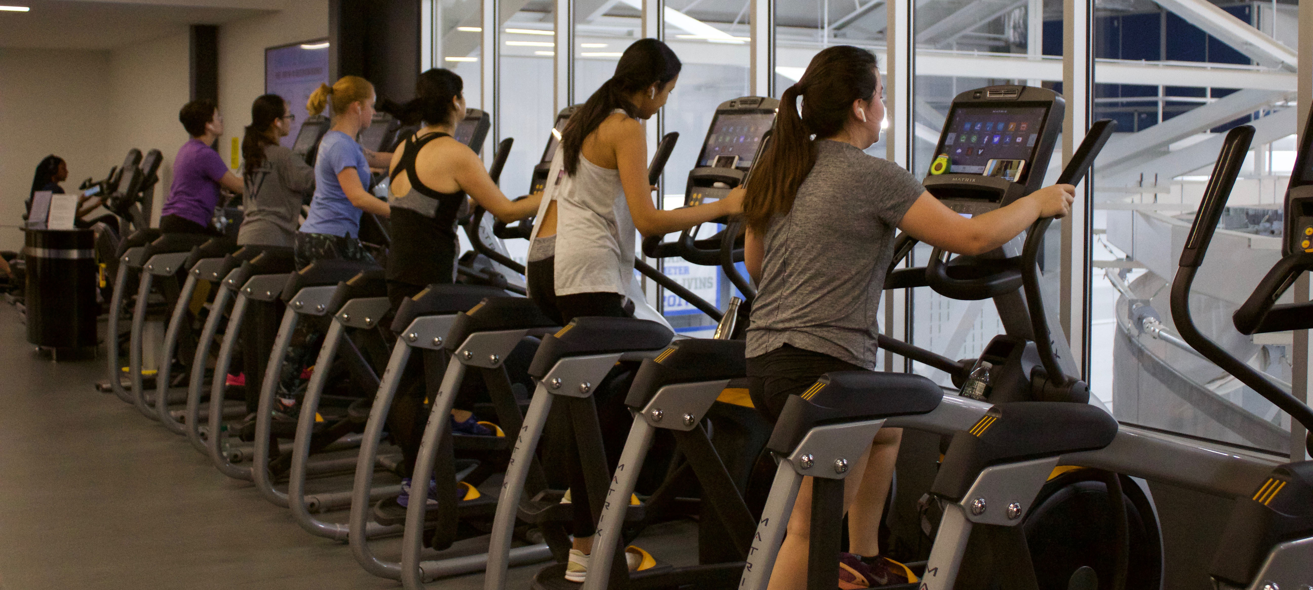 Each elliptical in the KSC is occupied with an exercising student. They are all facing away from the camera, focused.