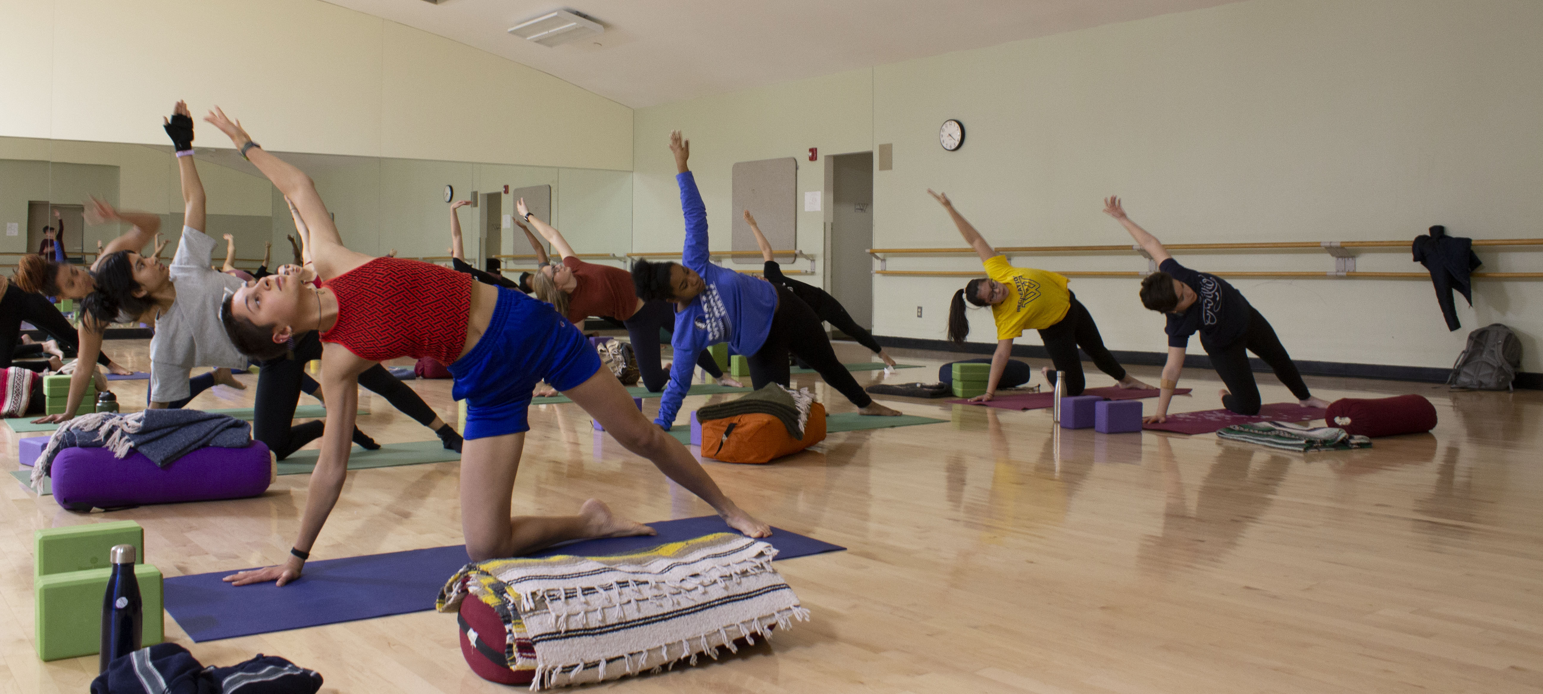 Students, facing the camera, are evenly spaced in the KSC dance room, executing a yoga move on their mats.