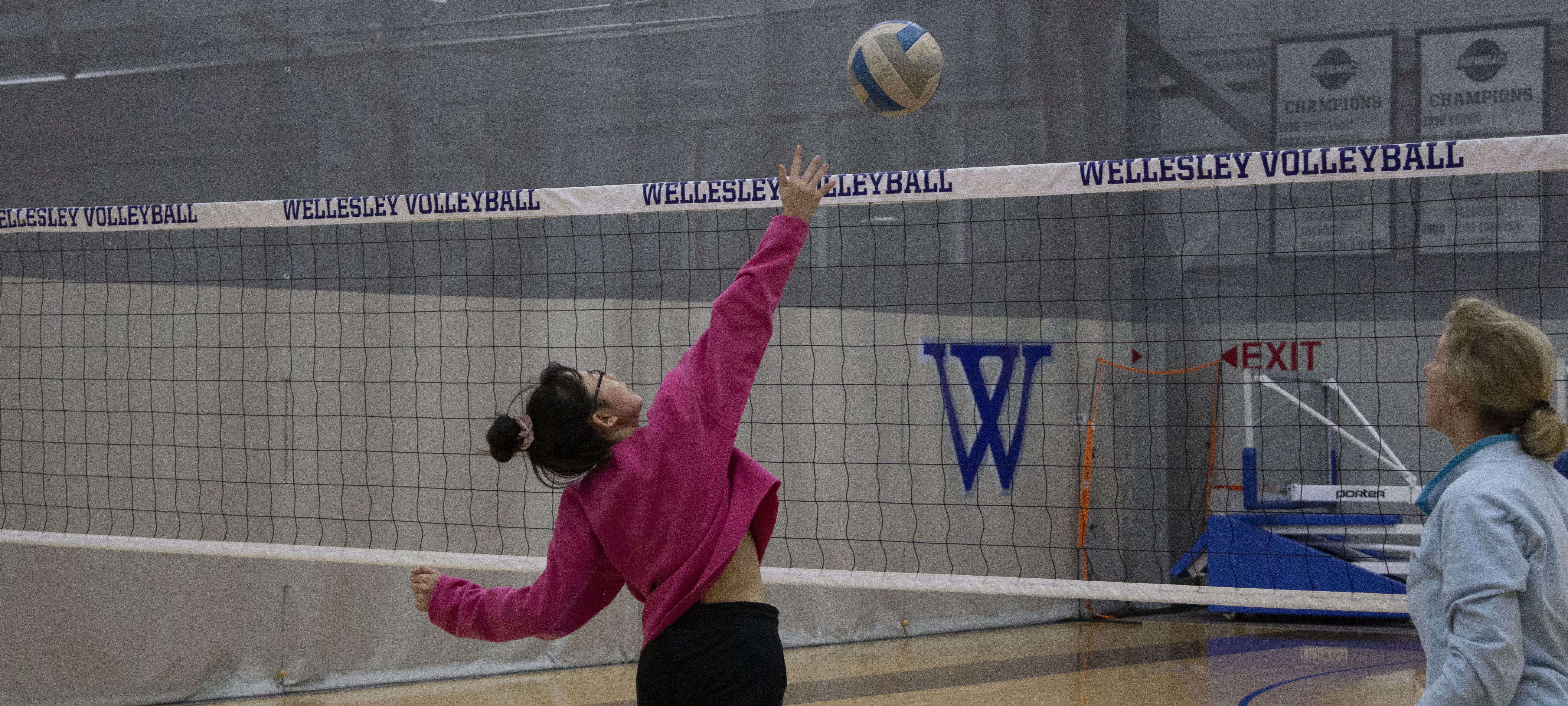 A student in front of a volleyball net with a centered blue W, throws a volleyball into the air to spike it. Their coach watches