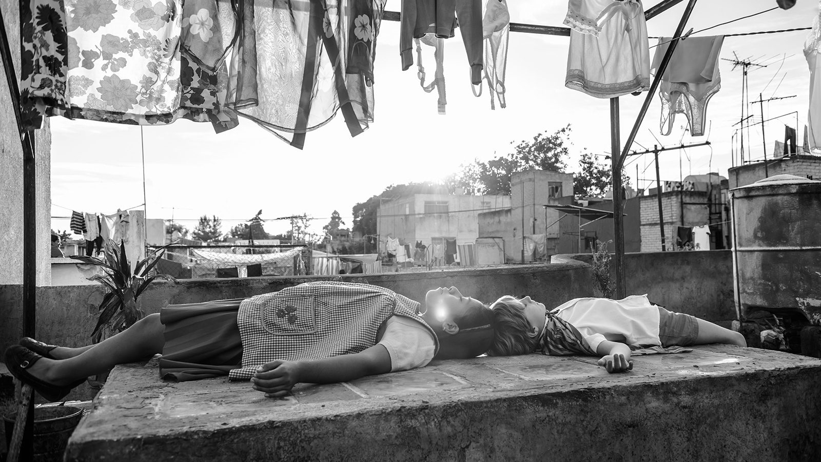 A still from the film Roma. A woman and a boy lie on a roof under a clothesline.