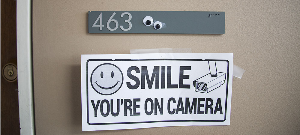 gray plaque with number 463 and two googly eyes on it, above white sign reading Smile, You're On Camera!