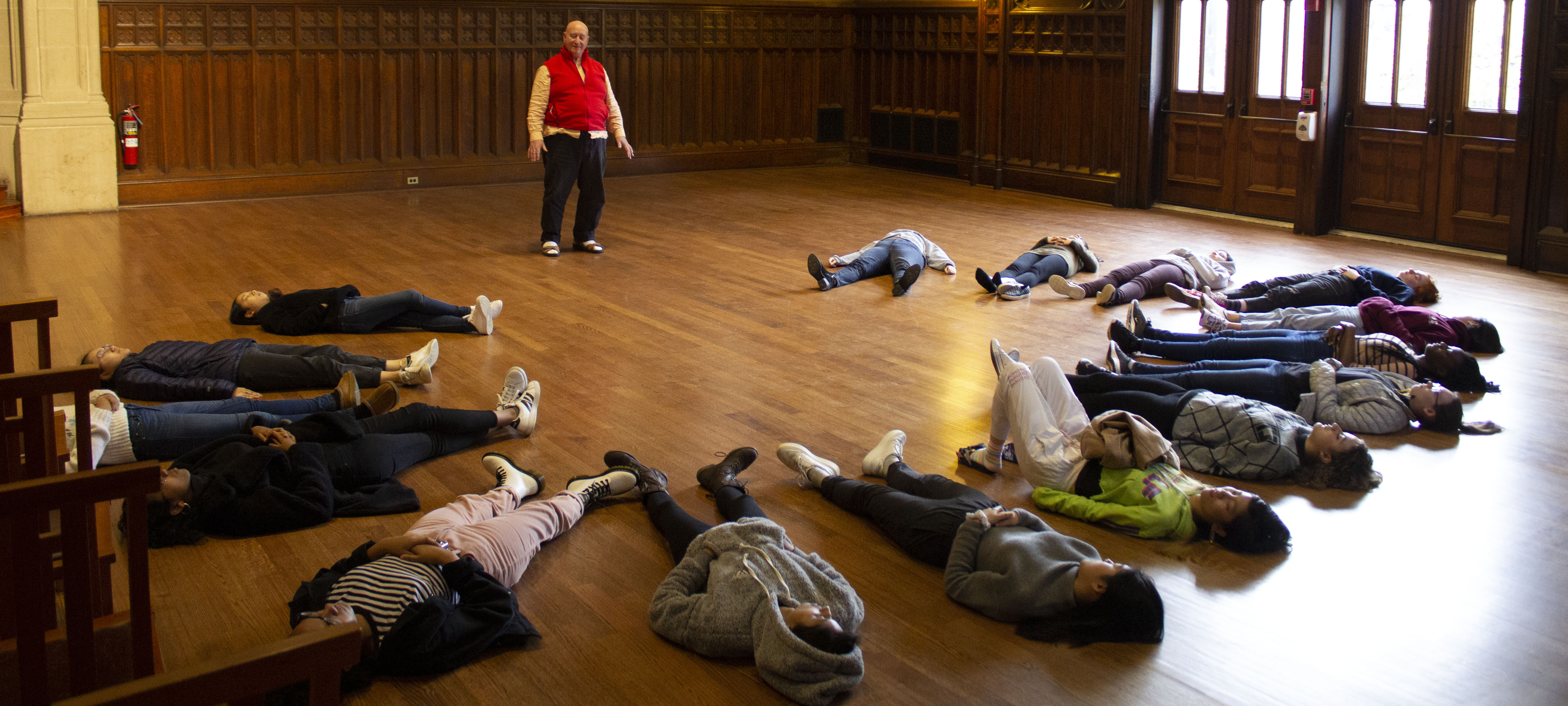 Students lie on the ground on their back in a circle as their teacher stands above them directly them to breathe.