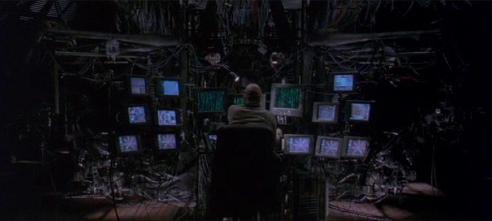 A still from the film the Matrix. A person looks at a stack of screens.