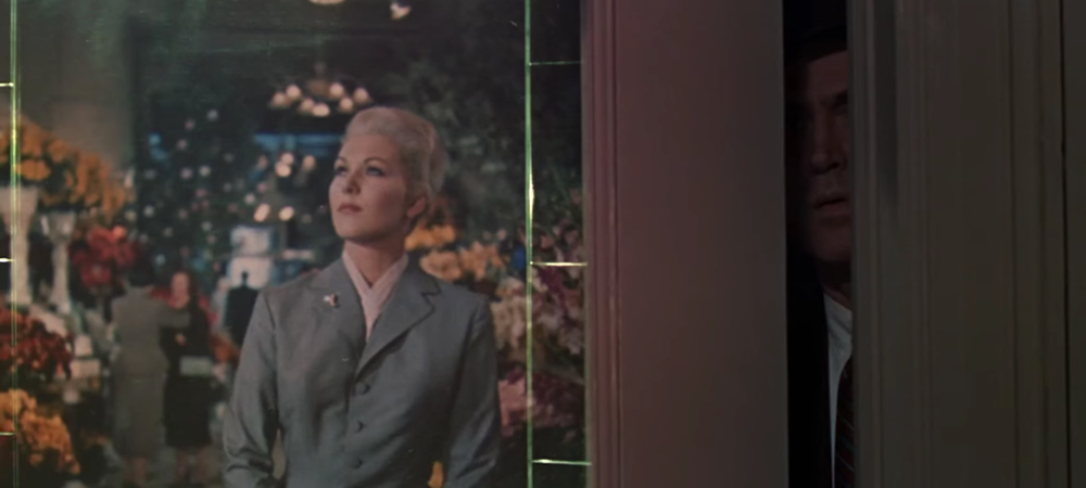 A still from the film Vertigo, a woman walks in a store and a man can be seen peering from an opening