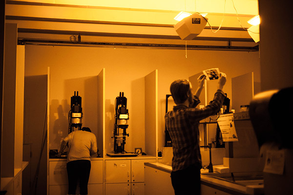 photographers working in the darkroom with yellow light