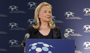Hillary Clinton at a podium with the Women in Public Service Logo behind her