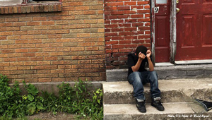 10-year old kid alone on a city stoop, head in hands