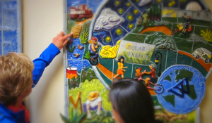 Faculty member and student look at a colorful ceramic mural of Wellesley sustainabilty initiatives