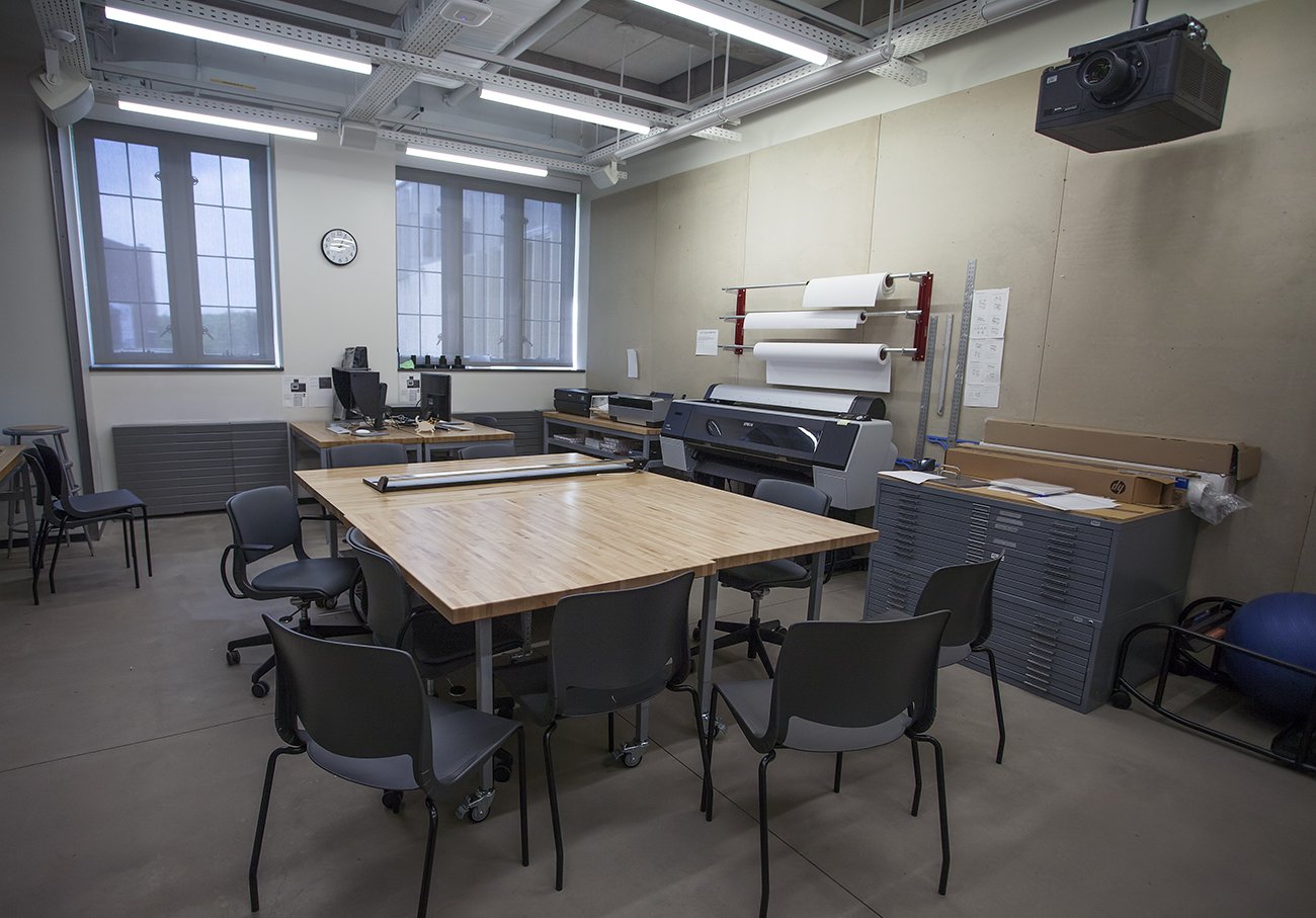 room with table, chairs, flat files, printer and rolls of paper, ceiling-mounted projector
