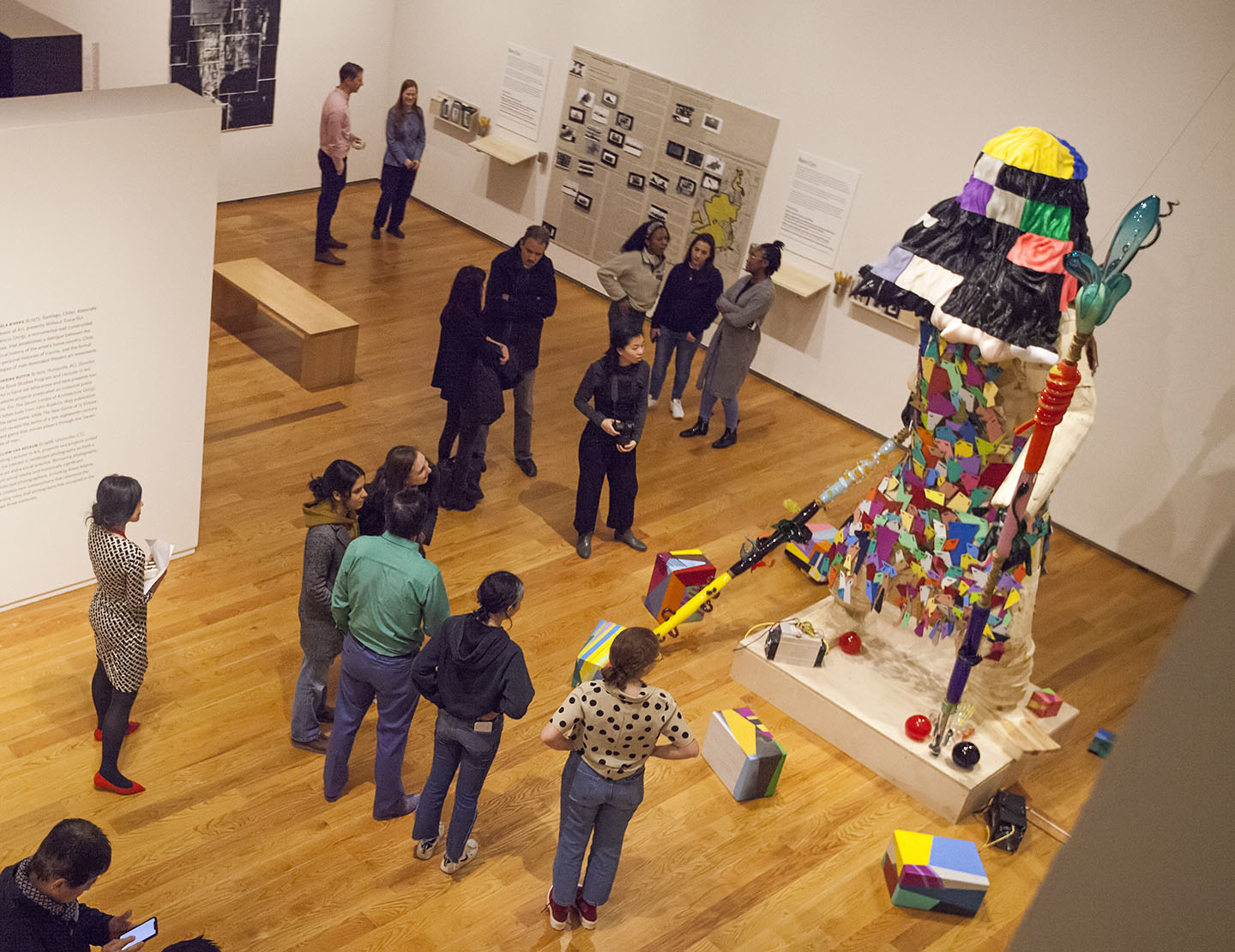 people looking at large figurative sculpture, gallery photographed from above