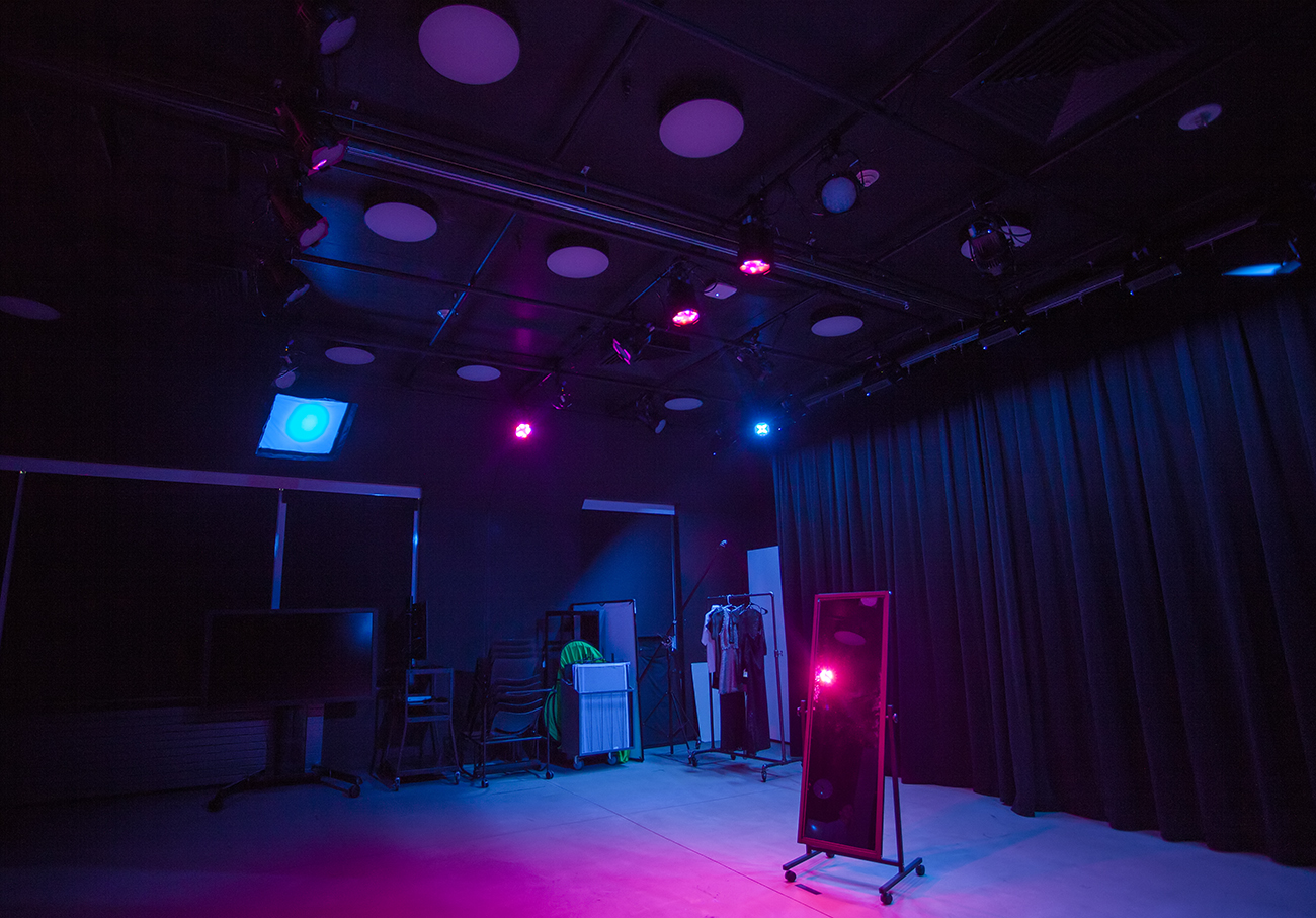 lighting studio with magenta and blue lights, stand up mirror in middle of room