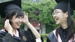 two Chinese students trying on graduation caps