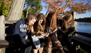 Four students share a bench by Wellesley's Lake Waban