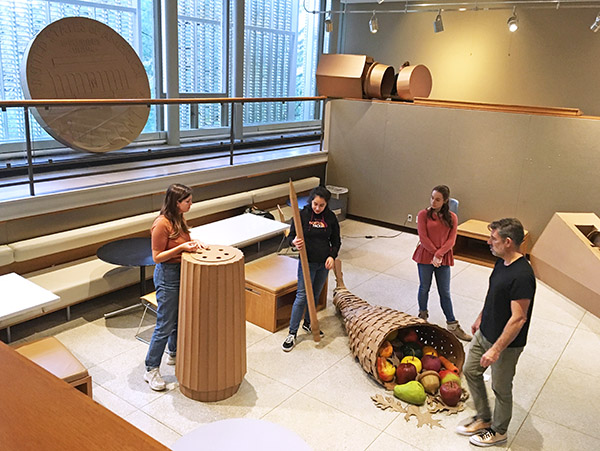 students and faculty install large cardboard sculptures in the Sculpture Court