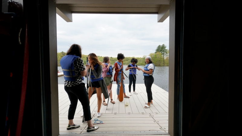 students in lifevests as seen through the boathouse doorway