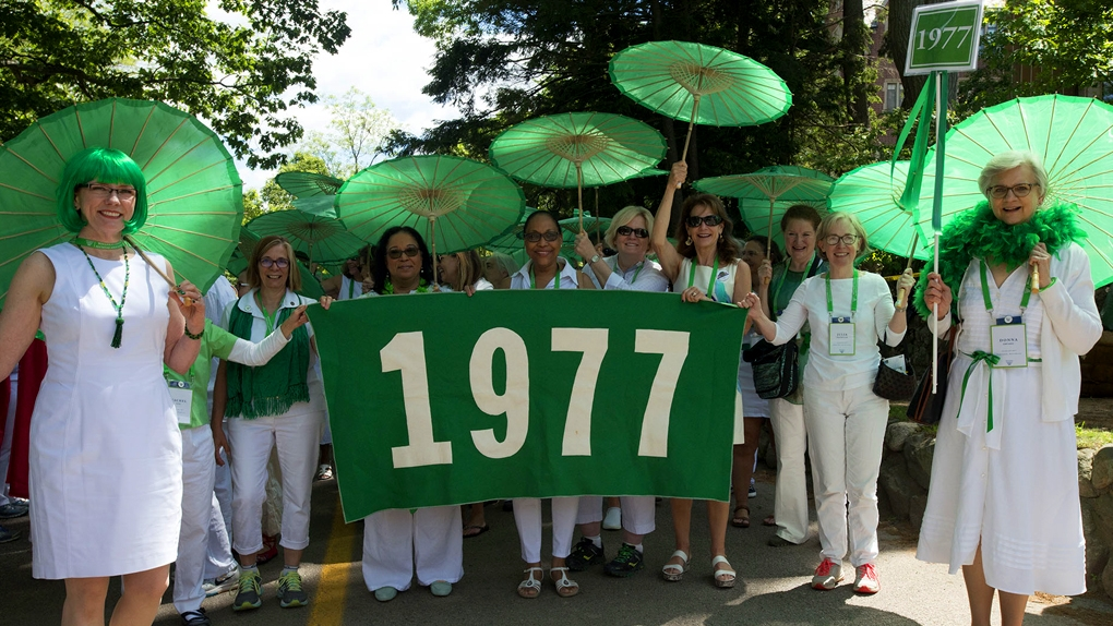 Green class alums decked out with green parasols and banners
