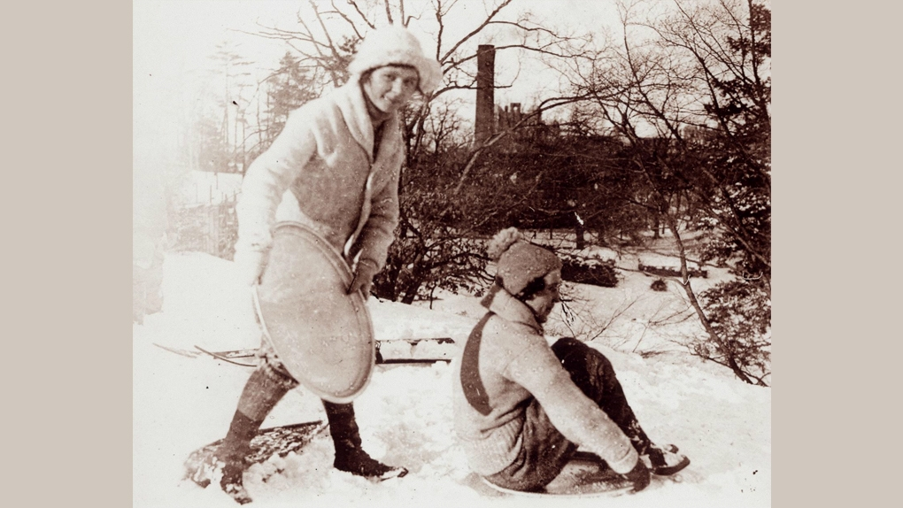 Two students sledding in 1925