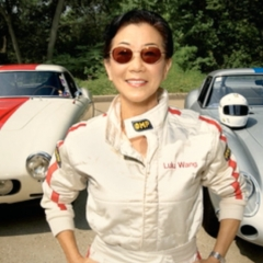 Lulu Chow Wang in front of two of her racecars
