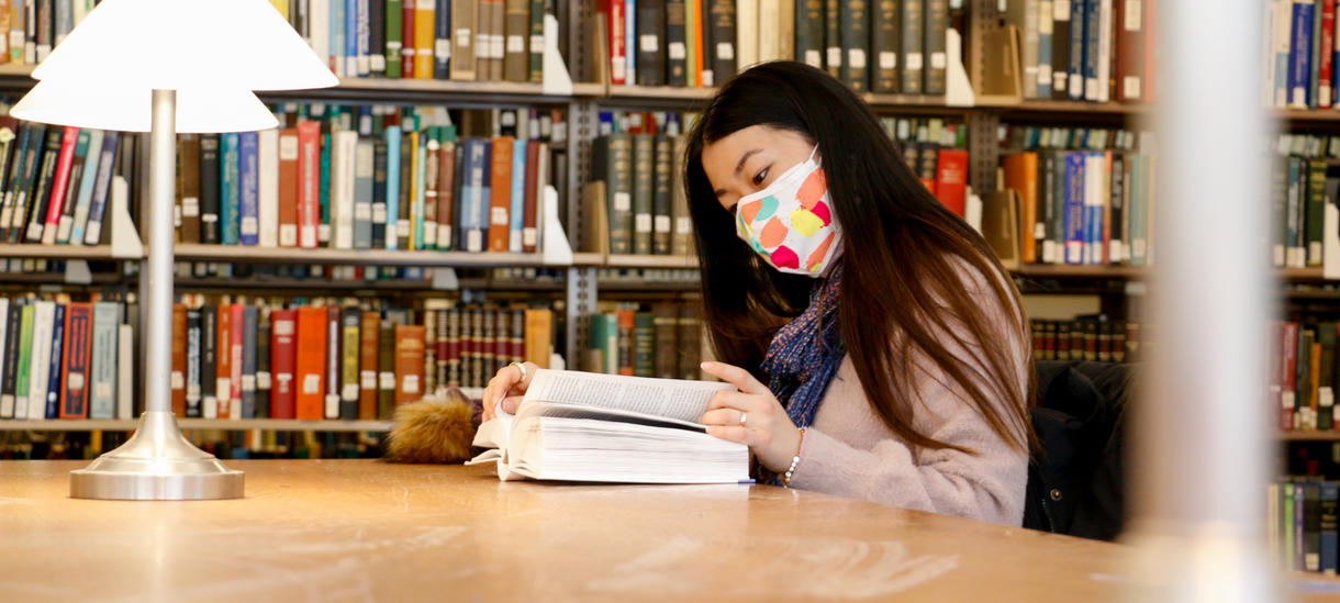 Student reading in the library in Fall 2020, wearing a colorful mask for COVID protection of herself and others.