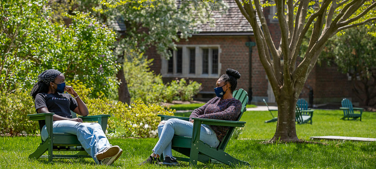 Picture of two students sitting outside, spring day, wearing masks, talking.