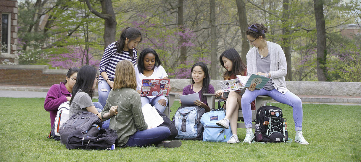 group of students chatting while sitting on the grass