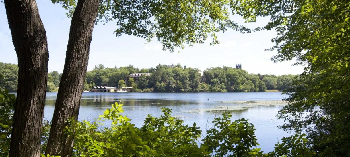 boat house and Galen Stone Tower as seen across Lake Waban
