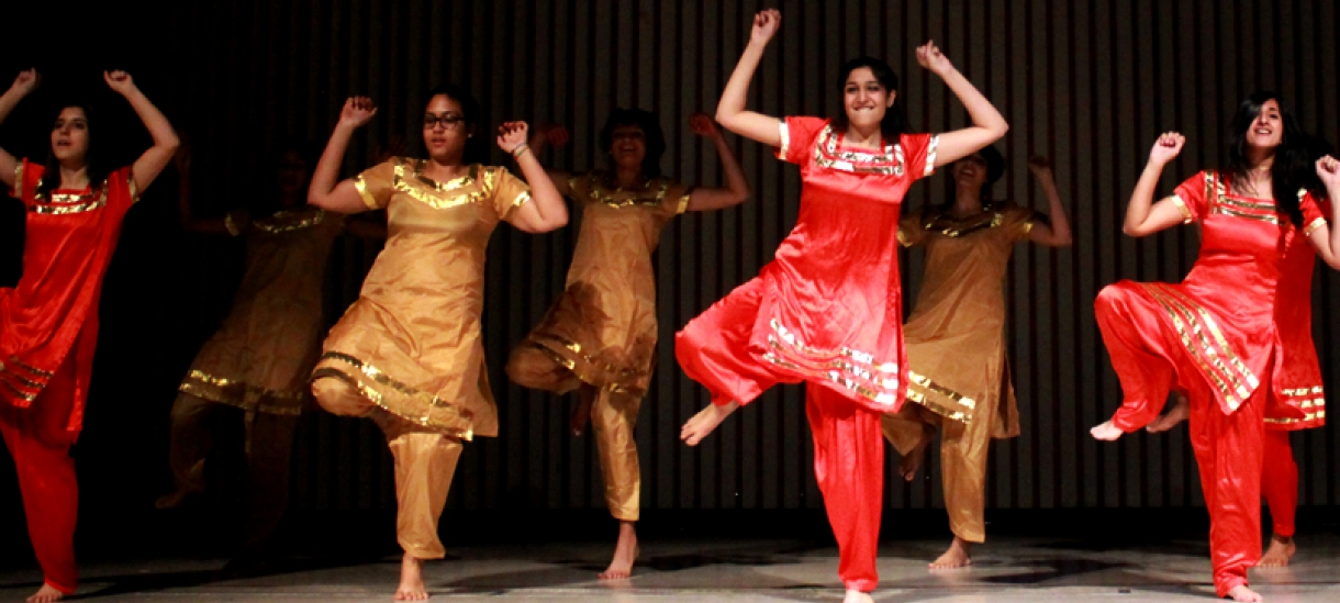 Students dressed in traditional South Asian attire perform a dance