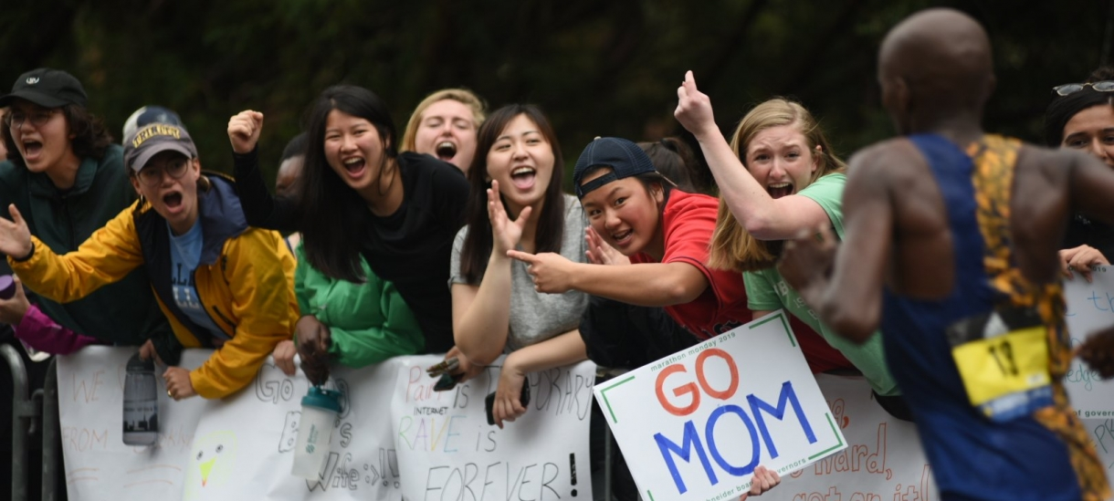 modern day students cheering with signs in the Scream Tunnel