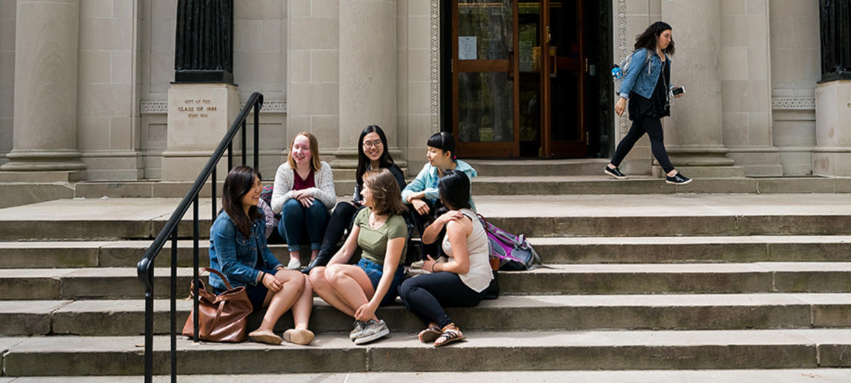 Wellesley students engage in lively discourse on the library steps.