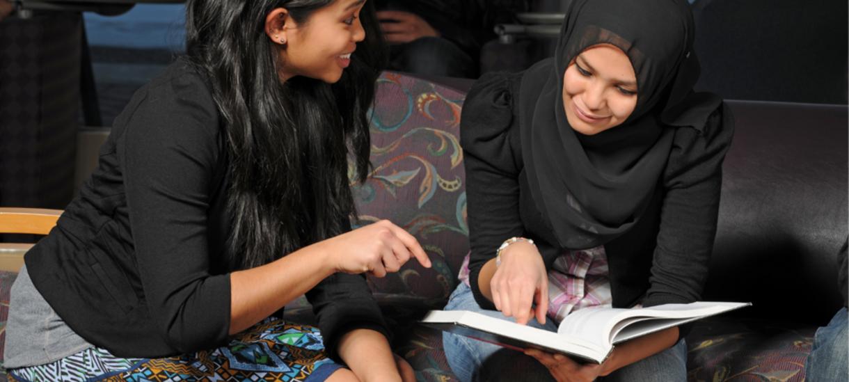 Two women sitting reviewing open book