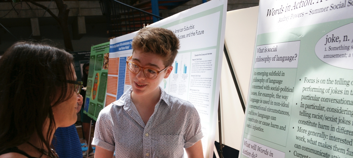 Student gives presentation on research to a member of the college community