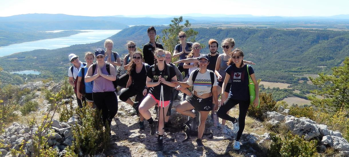 A group of about twenty young people gathered for a photo at the top of a mountain overlooking a large body of water.