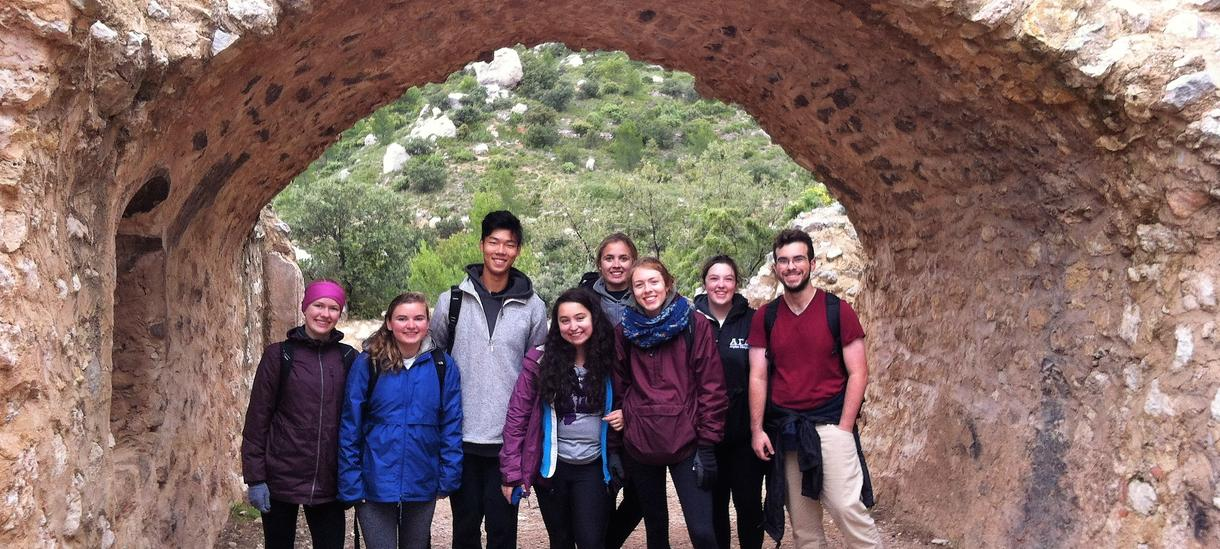 A group of eight students gathered for a photo underneath an arched rock structure, dressed in hiking gear.