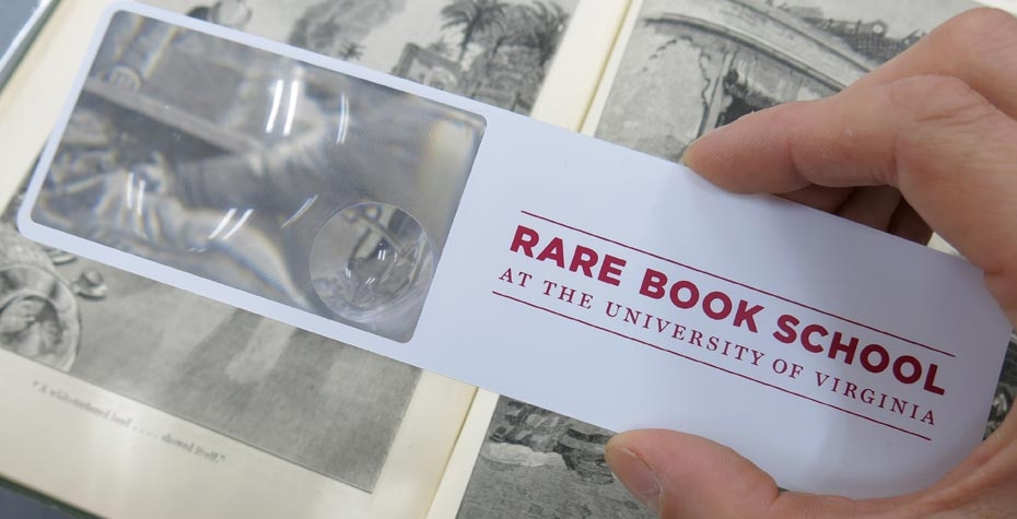 hand holding magnifier with logo for rare book school over old book