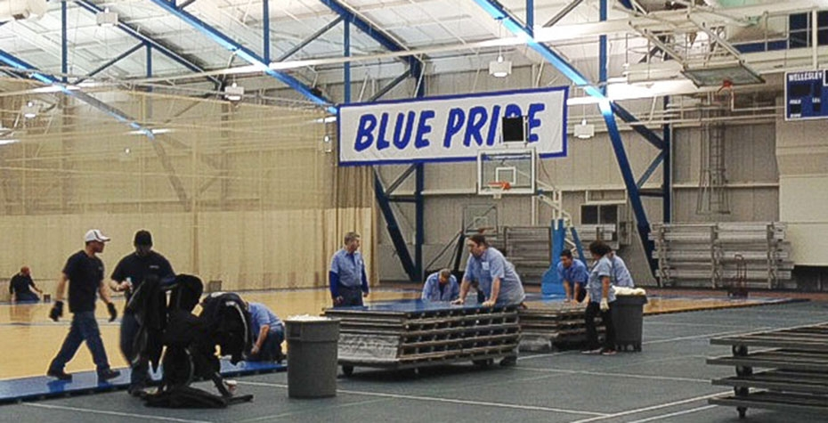 workers remove and stack panels from basketball floor