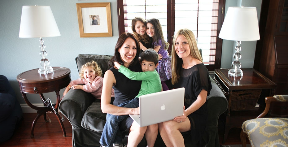 Erin Giglia, Laurie Rowen, and their respective children pose with a laptop on a couch