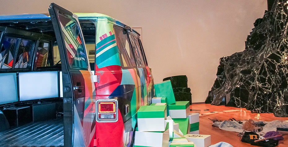 multicolored van with backdoors open revealing may screens inside, boxes and broken glass in installation to the right