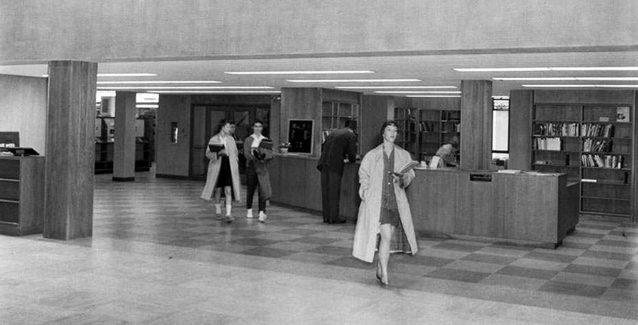 1959 photo: 3 students head out of library, wearing coats and bobby socks