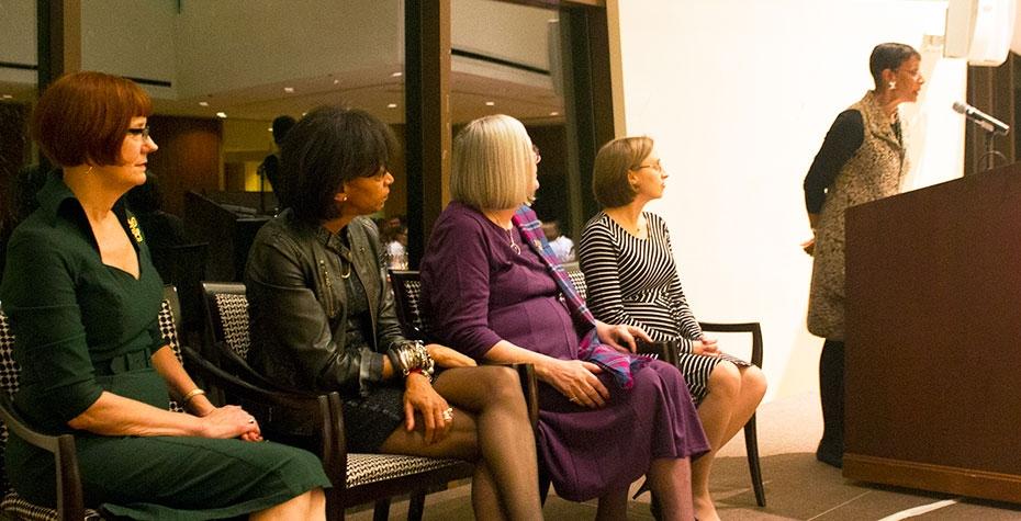Helen Kriz Marshall '77, Charlotte Hayes '75, Martha Reardon Bewick '62, and Whitney Shaffer Ackerman '03 seated, watch Karen Williamson at podium